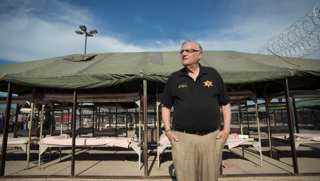 Pictured in 2013, former Maricopa County Sheriff Joe Arpaio stands near rows of empty bunks at Tent City Jail in Phoenix. Tent City is a major part of Arpaio's legacy.