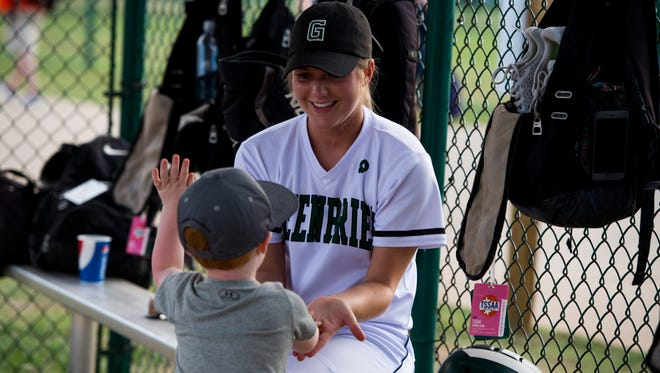 Savannah Dalton of Greenbrier high-fives her coach's son, 2-year-old Aaron Harris before her game against Elizabethon High School on May 23, 2017.