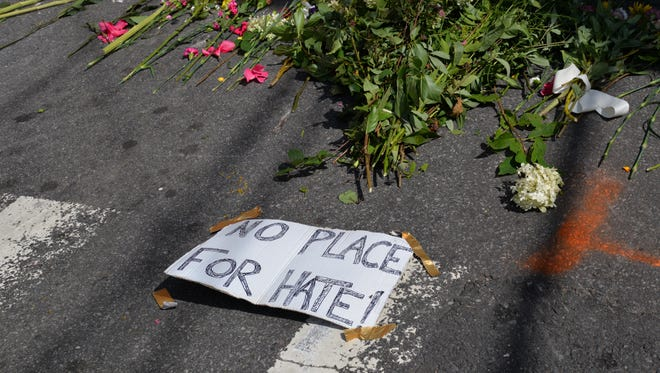 Flowers at the intersection of Fourth and Water streets in downtown Charlottesville on Sunday, Aug. 13, 2017. The day prior, a group of protesters was struck by a vehicle leaving one woman, Heather Heyer of Charlottesville, dead.