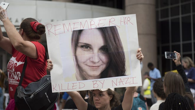 Protester carries an image of Heather Heyer during a demonstration against racism and the violence over the weekend in Charlottesville, Va.