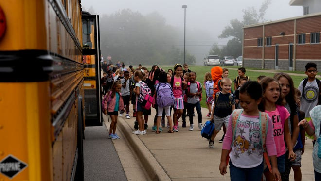 Hundreds of students from Rossview Elementary walk of the school buses before the start of their day on August 29, 2017.
