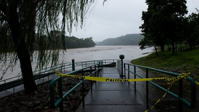 The Riverwalk in Clarksville is blocked off with caution tape as the Cumberland River begins to rise on September 1, 2017. It faces the Red River in the distance, where a search was underway for a man who fell into the river Friday night.