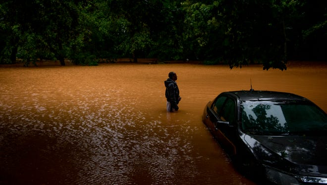 Willie Dunlap stands in his backyard next to his submerged car in Clarksville looking out at the floodwater in August 2017.