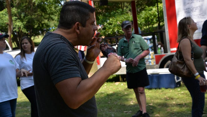 An attendee chows down at the third annual Virginia Food Truck Battle at the Frontier Culture Museum on Sunday, Sept. 3, 2017.
