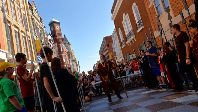 Chris Pugh as the Founder of Hogwarts Godric Gryffindor sets up a life size version of chess during the Queen City Mischief and Magic in downtown Staunton on Sunday, Sept. 24, 2017.