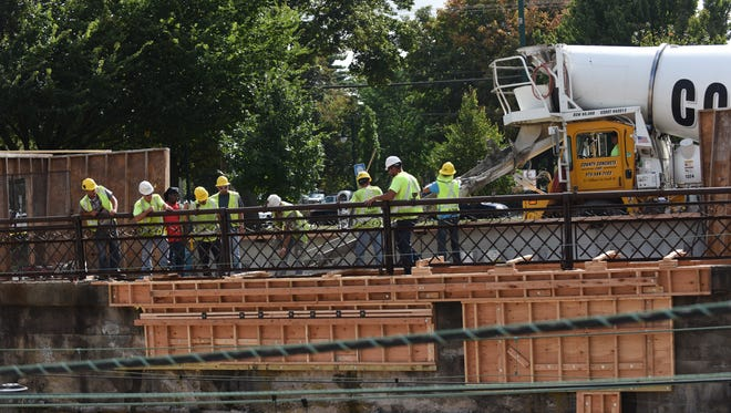 Workers repair the damaged concrete retaining wall at Summit Train Station on Wednesday.