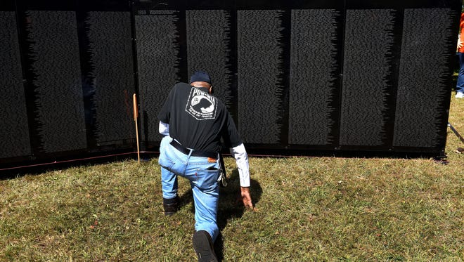 """Freddie Owens looks for his friend's name on The Wall That Heals, a half-scale replica of the Vietnam Veterans Memorial in Washington D.C., Wednesday, Oct. 4, 2017. Owens said after finding the name, """"Paul Lemay was the first guy killed in my unit in Nam in 1959."""""""