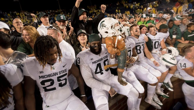 The Michigan State Spartans celebrate with the Paul Bunyan trophy after defeating Michigan 14-10.
