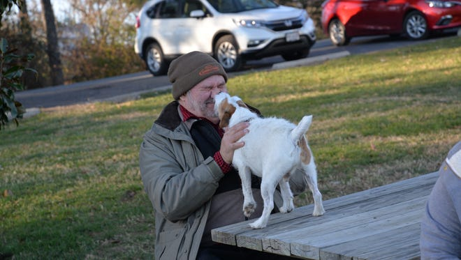 Harry King getting a kiss from a dog at Coyner Springs Park in Waynesboro on Thursday, Nov. 23, 2017 for an annual Thanksgiving meal with their furry friends.