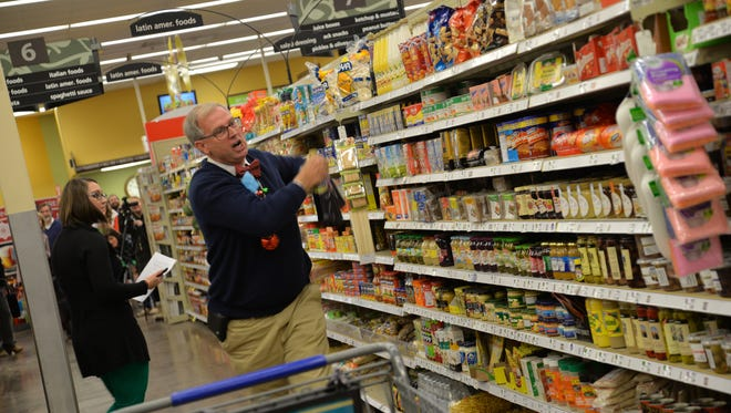 Roger Boles of Home Instead Senior Care participates in the Blue Ridge Area Food Bank's Shop to Stop Hunger event at the Staunton Kroger on Thursday, Dec. 14, 2017.
