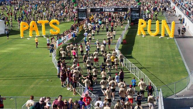 Participants cross the finish line during the 2017 Pat's Run at Sun Devil Stadium.