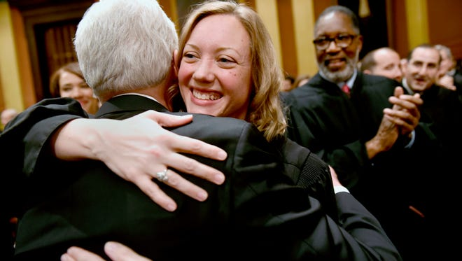 Gov. Rick Snyder is greeted by State Supreme Court Justice Elizabeth T. Clement.