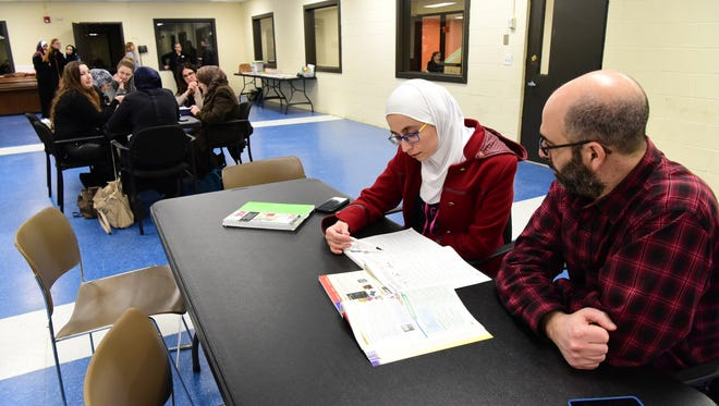 Liza Abdulah learns English with a volunteer, Reid Paul, at the Wayne YMCA. The English lessons are offered through NJ ReBuild, a program that helps refugees learn the language and culture and build ties in their new community, and offers guidance on housing, medical care and other needs.