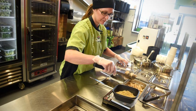Lisa Schulte prepares an order with fresh ingredients on the line Wednesday, March 14, at Quarks American Bento in St. Cloud. Quarks received a food safety award from the city of St. Cloud following their most recent full-restaurant inspection.