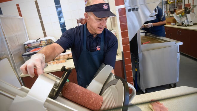 Franchisee Bart Crockett slices meat for a sub to order at Jersey Mike's Subs Monday, March 26, in St. Cloud.