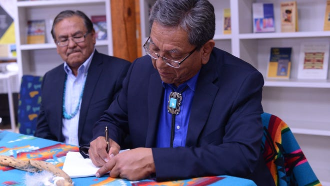 Navajo Technical University President Elmer Guy, left, watches Navajo Nation President Russell Begaye sign the tribal council resolution to provide funding for student housing on May 1 in Crownpoint.