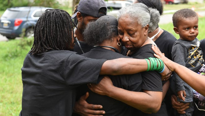 Aufelia Palmer (center), mother of Antonio Walker, gets a hug from her mother Loretta Taylor (right), moments after a  balloon release in remembrance of Antonio Walker, who was killed July 12, 2011.