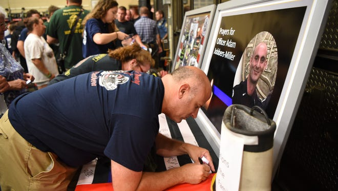 Nick Cifelli from Lincoln Park signs a flag during a prayer vigil for Adam Jobbers-Miller at P.O.L. Fire Company two in Wayne on Friday July 27, 2018.