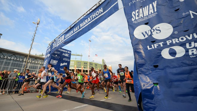 The elite runners sprint out of the starting gate at the Cellcom Green Bay Marathon Sunday, May 18, 2014.  Jim Matthews/Press-Gazette Media