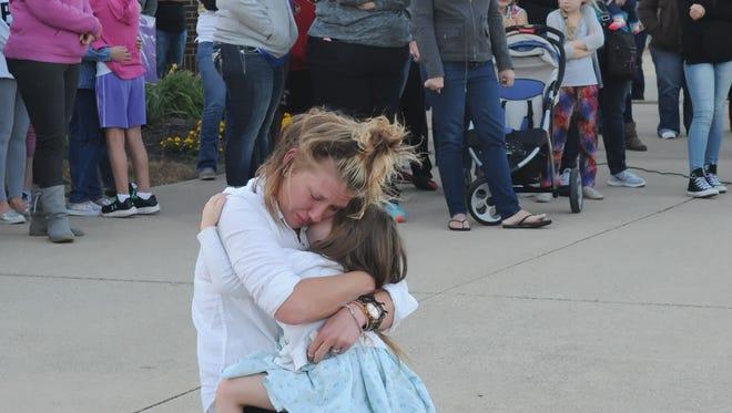 Bobbie Adams comforts her daughter Addilynne as mourners gather to remember slain art teacher Kristi Redmon in the playground of Edgelea elementary school Sunday.