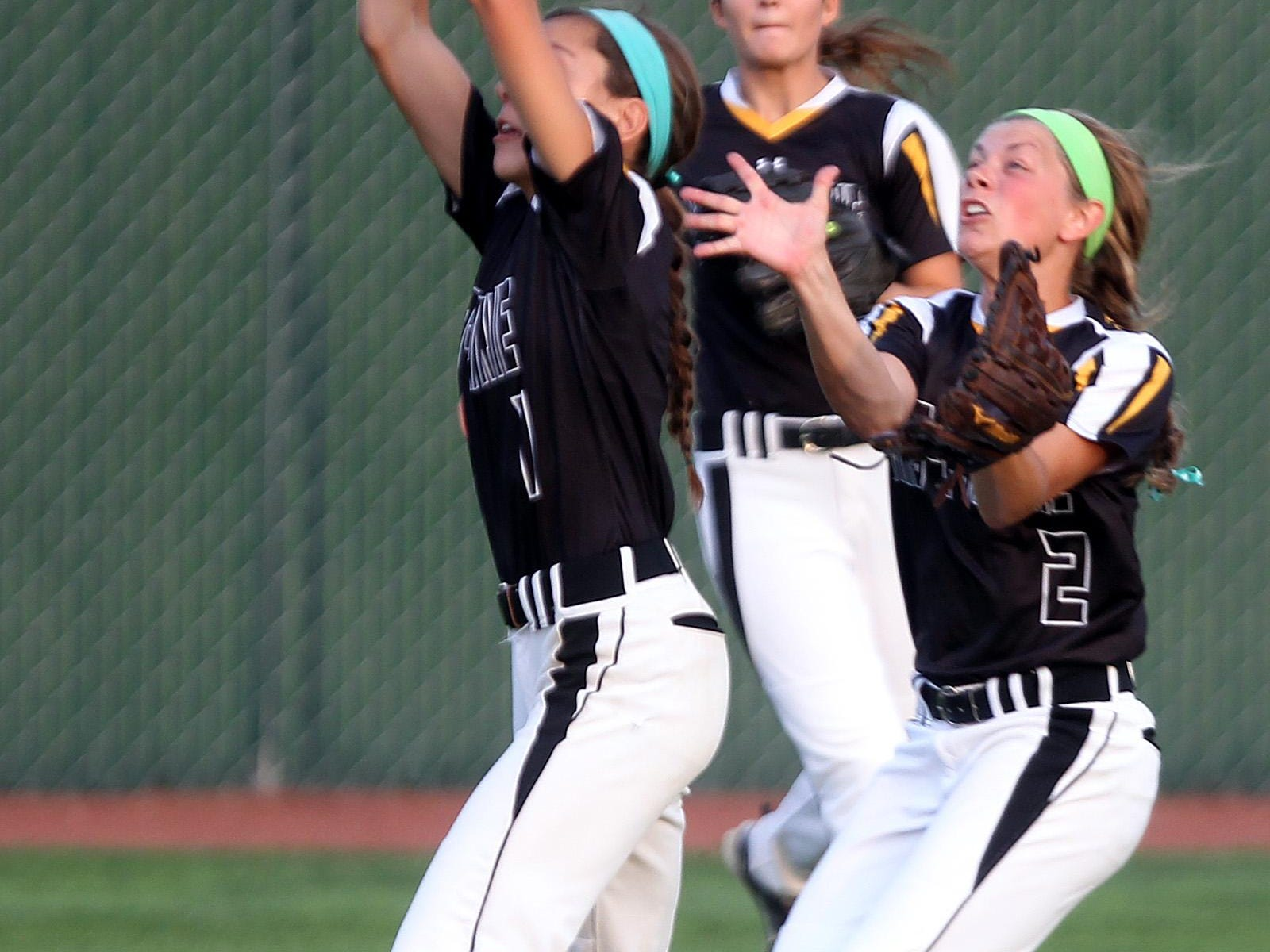 Mid-Prairie's Alex Rath avoids Lexi Duwa and catches the ball in centerfield during their regional game against Mid-Prairie at Solon on Friday, July 10, 2015. David Scrivner / Iowa City Press-Citizen