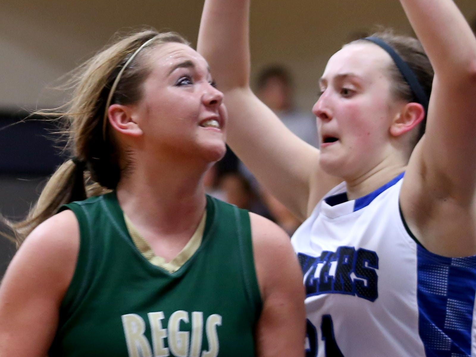 Regis' Abigail Frith (2) eyes the basket while being defended by Western Mennonite's Lexi Pack (21) in the Regis vs. Western Mennonite girl's basketball game at Western Mennonite High School on Wednesday, Feb. 17, 2016.