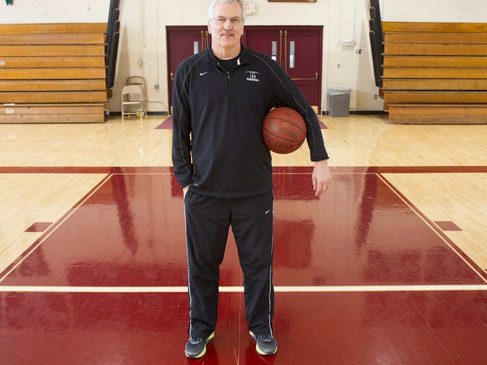 Iowa Mennonite School head coach Dwight Gingerich poses in his school's gym on Wednesday, Feb. 11, 2015.