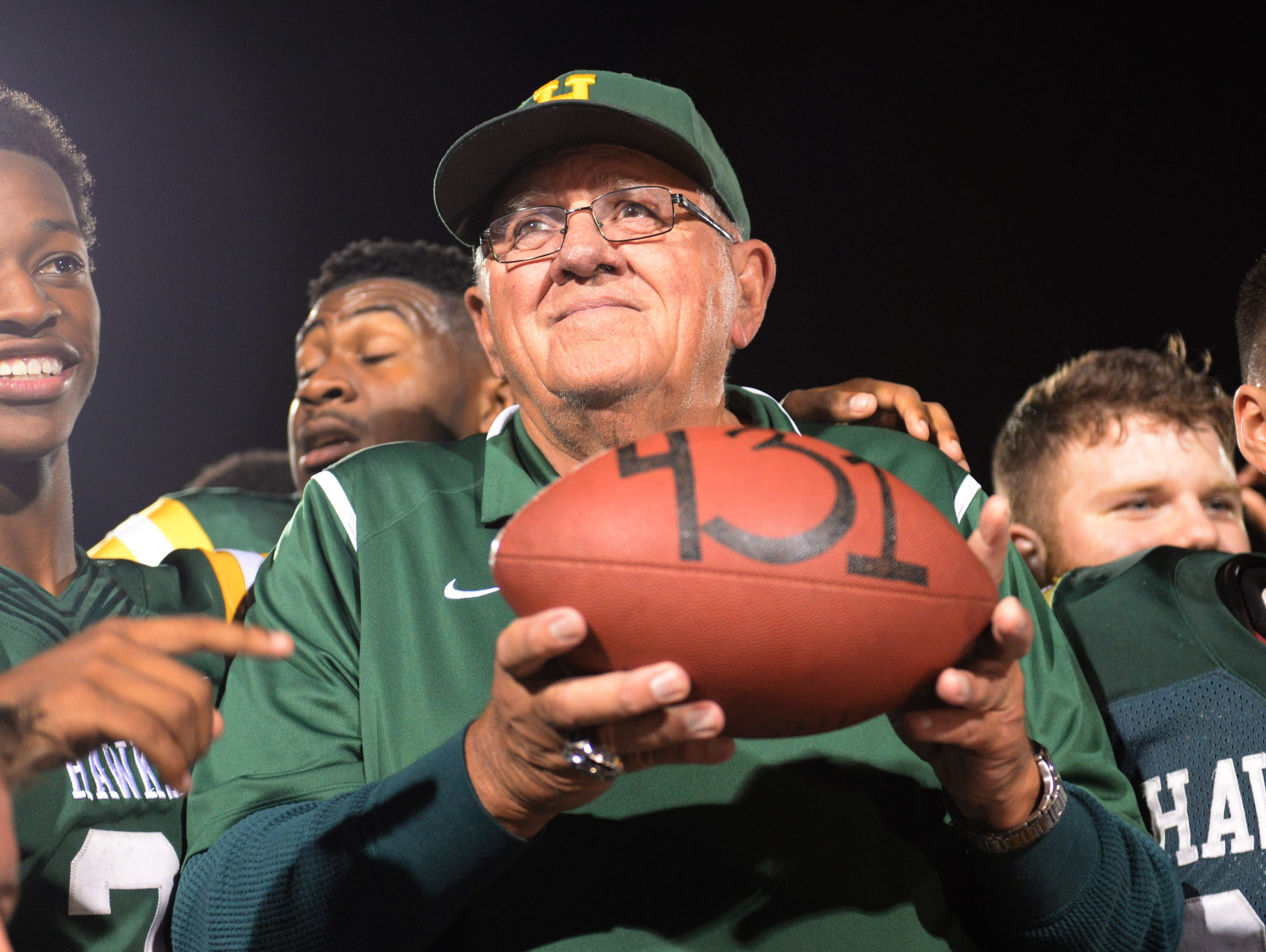 "Coach John Herrington holds the game ball with ""431"" written on it after defeating  Oak Park 17-14 on Oct. 6, 2017."