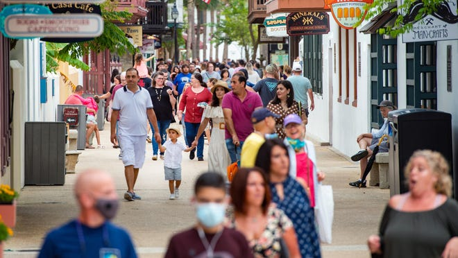 People walk down St. George Street in St. Augustine on June 5, and only a few in the crowd are seen wearing masks.