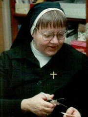 Sister Rita Pearce, SCSC, trimming stamps in Merrill