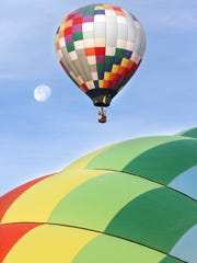 A balloon floats in front of the moon as another inflates at the KLAQ Balloonfest in this file photo.