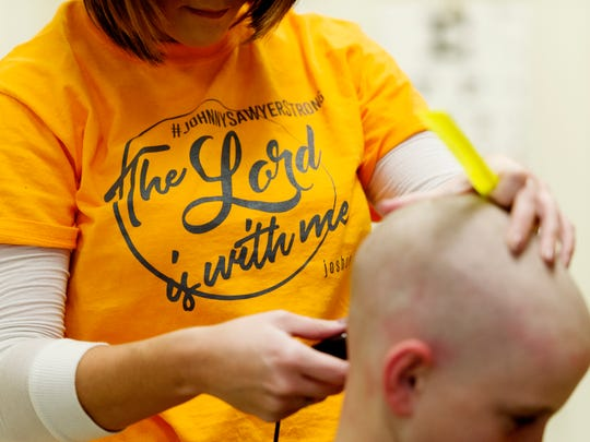 Amanda Mounger shaves Seth Blankenship,10,  head to show his support for his schoolmate Johnny Sawyer Dyer, who has Acute Myeloid Leukemia, at Gibbs Family Practice in Corryton, Tennessee on Saturday, January 28, 2017.