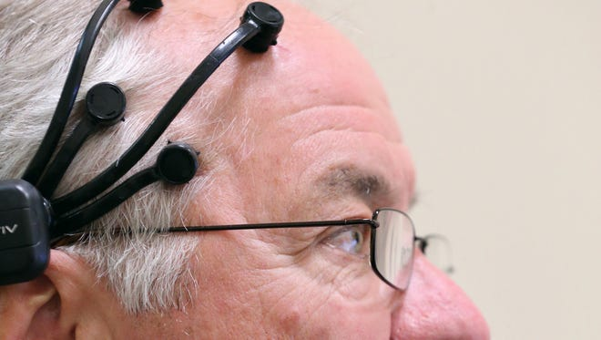 John MacWherter views political advertisements with a emotive head set hooked up to his head during a study at the Taylor Institute for Direct Marketing on Tuesday, April 12, 2016 in Akron, Ohio. The headphones with moistened tentacles touch the scalp and measures brain waves. A long, narrow bar sits below the computer screen in front of them and record eye movement.  (Phil Masturzo/Akron Beacon Journal)