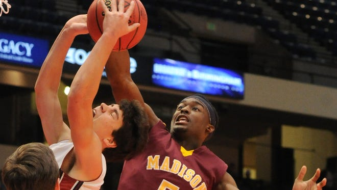 Madison Academy's Josh Langford, right, blocks a shot by Montgomery Academy's Barton Lester during a state semifinal game in Birmingham, Ala., on Feb. 24, 2015.
