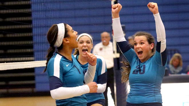 Siegel's Kristin Demonbreun (20), right celebrates with Hannah Adams (31), center, and Asha Phillips (7) near the end of the 3rd set in the TSSAA Class AAA Sectional against Walker Valley on Thursday, Oct. 15, 2015, at Siegel.