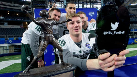 Michigan State quarterback Connor Cook (18)  takes a selfie with his Johnny Unitas Trophy and teammates at Media Day for the Cotton Bowl on Tuesday December 29, 2015 at AT&T Stadium in Arlington, Tx.