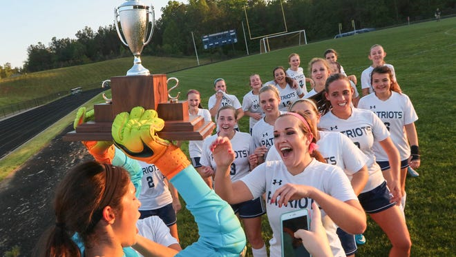 Powdersville sophomore goalkeeper Jeanette Campbell, left, carries the region II-AAA championship trophy after beating Carolina Academy 3-2 in Powdersville on Wednesday.