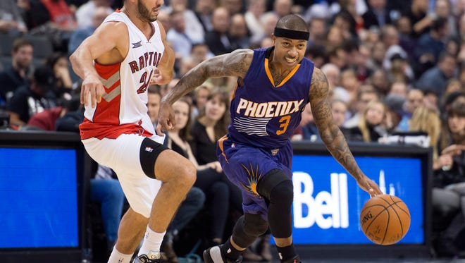 Phoenix Suns' Isaiah Thomas drives past Toronto Raptors' Greivis Vasquez on Nov. 24, 2014 in Toronto.