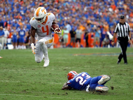 FILE - In this Saturday, Sept. 16, 2017, file photo, Tennessee running back John Kelly (4) leaps over Florida defensive back Chauncey Gardner Jr. (23) for extra yardage on a run in the second half of an NCAA college football game, Saturday, Sept. 16, 2017, in Gainesville, Fla. Tennessee's challenge this week has been focusing on Massachusetts when everyone around town is asking about what went wrong against Florida. (AP Photo/John Raoux, File)
