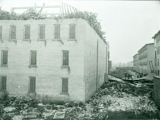Chairs litter the ground around Crocker Chair Warehouse B, roofless with chairs on the fourth floor. Tornado of 1900.