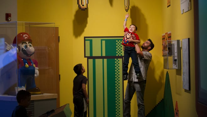 Dennis Davidson of Greece lifts his son Deacon, 8, up to touch a coin at the Nintendo exhibit on Saturday.