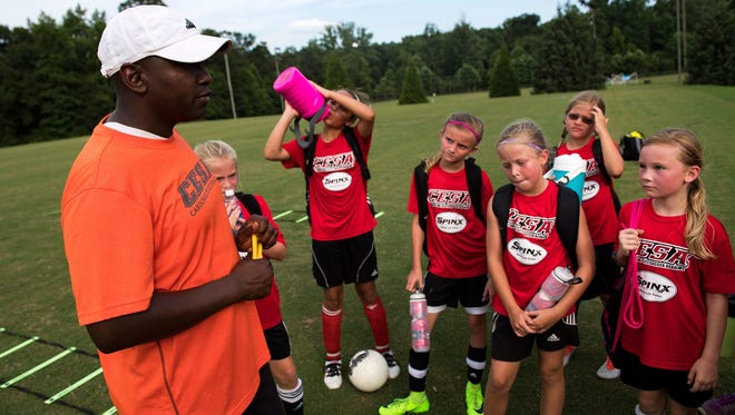 CESA coach Terrance Shearn speaks with girls on his U10 and U11 teams after a recent practice at the Wenwood Soccer Complex.