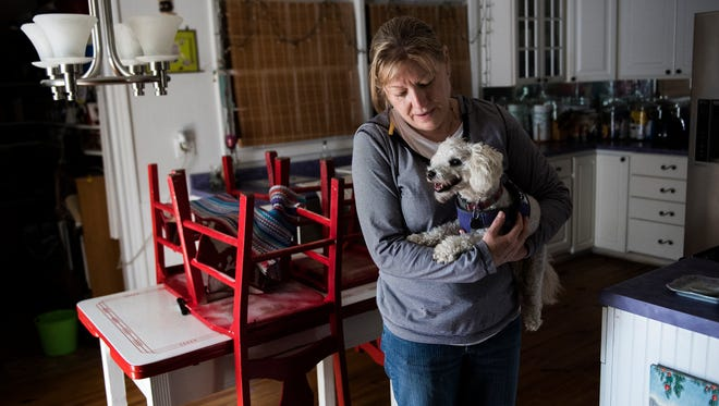 Susan Hill holds her dog Mac after entering her Tybee Island home for the first time to assess flood damage from a record high tide and Tropical Storm Irma on Tuesday, Sept. 12, 2017.