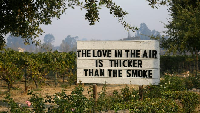 A sign about the recent wildfires stands in a vineyard outside the Cline Cellars winery on Oct. 16, 2017, in Sonoma, Calif.