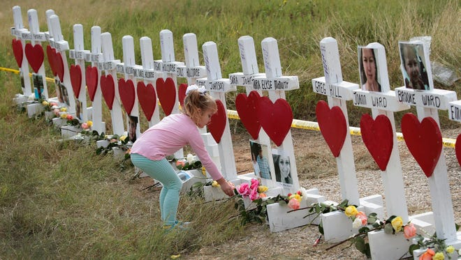 Four-year-old Shaelyn Gisler leaves a flower at a memorial where 26 crosses were placed to honor the 26 victims killed at the First Baptist Church of Sutherland Springs on Nov. 9, 2017 in Sutherland Springs, Texas.