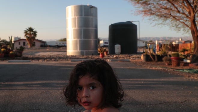 Helen Negrete, age 4, bikes past two water tanks which are used by the fire department, Thermal, Calif., Wednesday, April 4, 2018.  Her neightborhood relies on a contaminated well for water and residents have been provided filters to make the water safe for drinking.