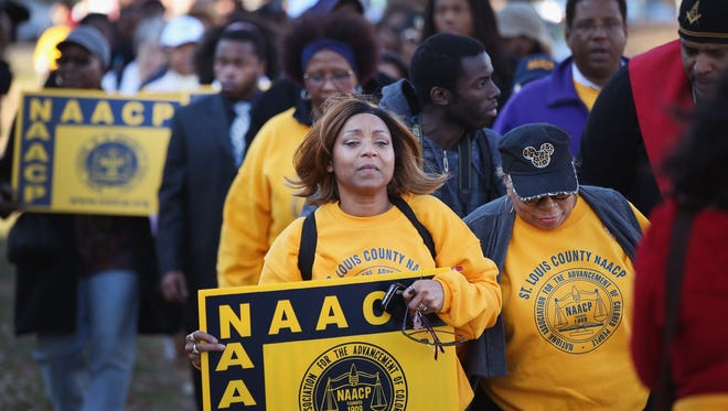 Members of the NAACP and their supporters arrive at the Michael Brown memorial Saturday in Ferguson, Mo., to start the Journey for Justice, a seven-day, 120-mile march from the memorial to the governor's mansion in Jefferson City, Mo.