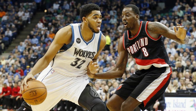 Minnesota Timberwolves' Karl-Anthony Towns, left, drives around Portland Trail Blazers' Al-Farouq Aminu in the first half of an NBA basketball game, Monday, Nov. 2, 2015, in Minneapolis.