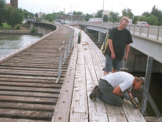 Doug Wicks, assisted by Ron Siefke, removes railings