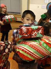 Deerfield Elementary School student Mason McNatt gathers up presents that he helped raise money to purchase for needy families as part of Deerfield first-graders' recent lesson on empathy. The money raised bought essentials and a few extras for a family in Novi and four families in West Bloomfield.